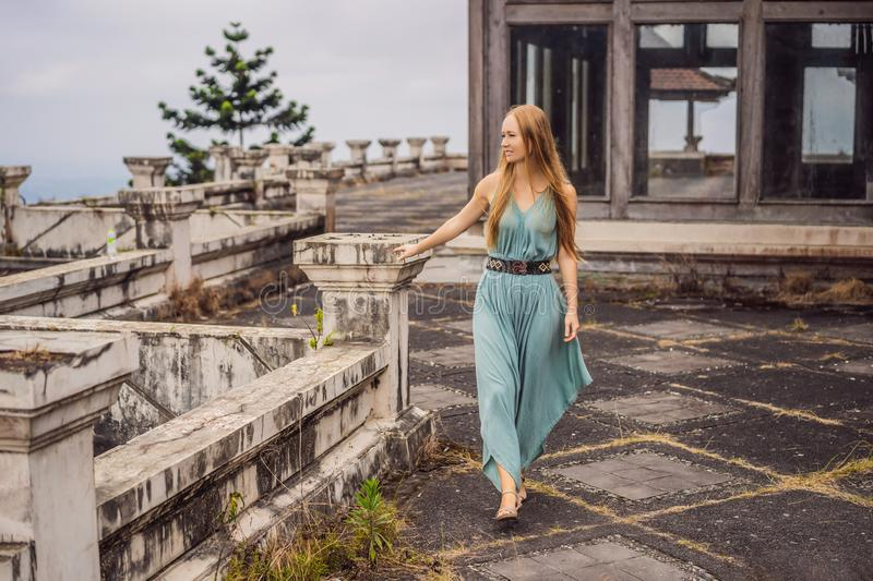 Woman tourist in abandoned and mysterious hotel in Bedugul. Indonesia, Bali Island. Bali Travel Concept royalty free stock photography