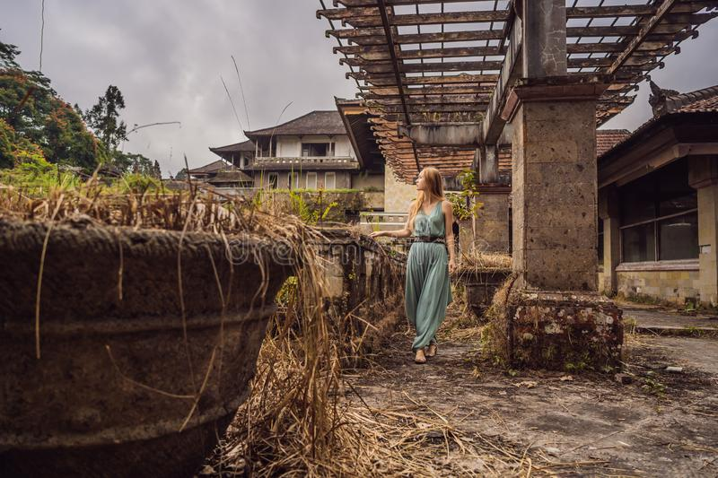 Woman tourist in abandoned and mysterious hotel in Bedugul. Indonesia, Bali Island. Bali Travel Concept royalty free stock image