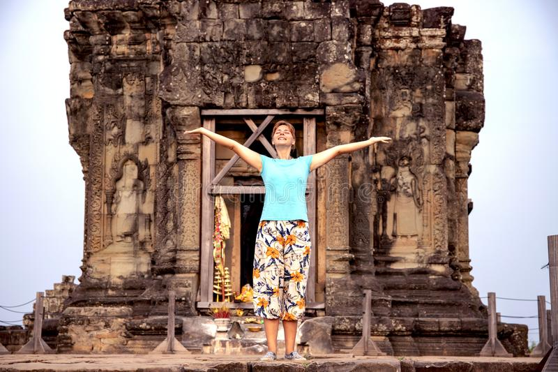Woman tourist in Angkor Wat temple, Cambodia. Morning yoga in Phnom Bakheng temple. Sunrise point in Angkor. Happy tourist in ancient temple ruin. Khmer place royalty free stock image