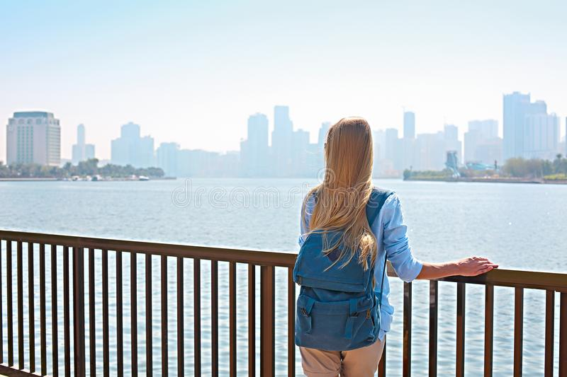 Woman tourist with backpack and panorama of Sharjah and man-made lake, Sharjah, royalty free stock photo