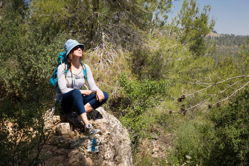 Woman tourist backpacker sitting resting stone hiking forest landscape stock photography