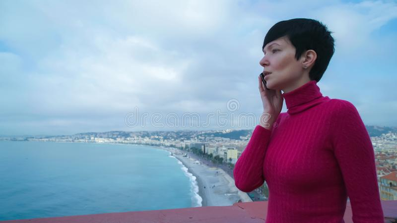 Woman tourist calling on the smartphone stand on the observation deck. Female using app on the mobile phone. City view with sea and beach. Caucasian model stock photography