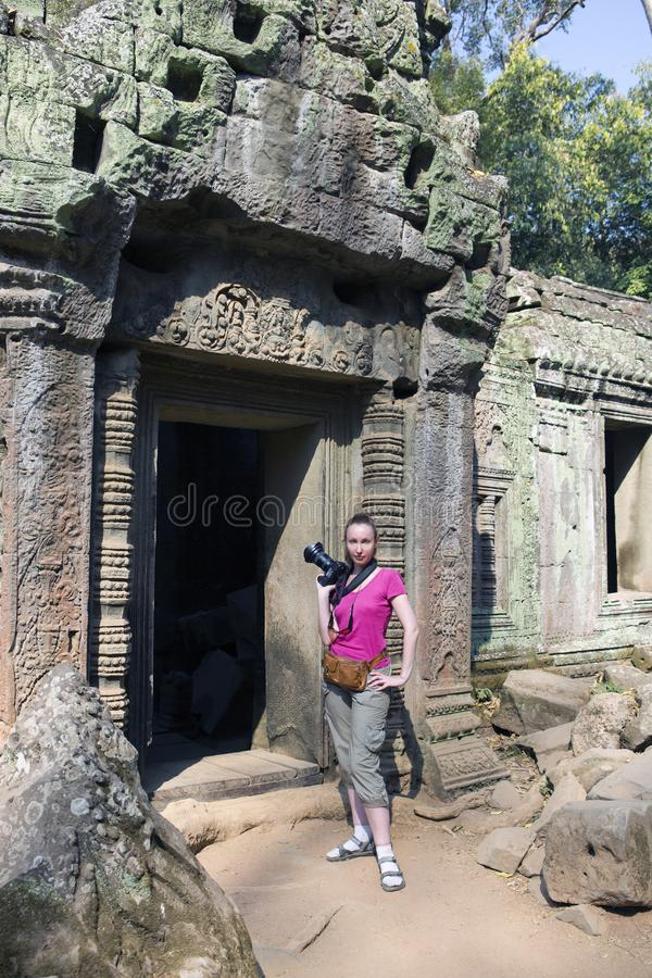 The woman the tourist with the camera at an entrance to ruins of the destroyed temple, Siem Reap, Cambodia royalty free stock photo