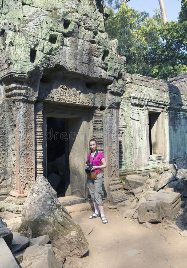Woman the tourist with the camera at an entrance to ruins of the destroyed temple, Siem Reap, Cambodia stock photography