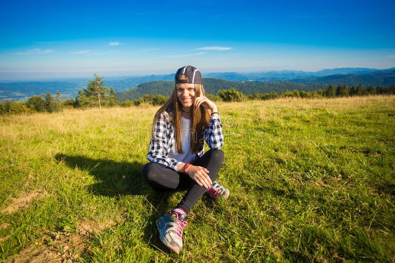 Woman tourist in cap on top of hill enjoying view of mountains. Travel concept royalty free stock photos