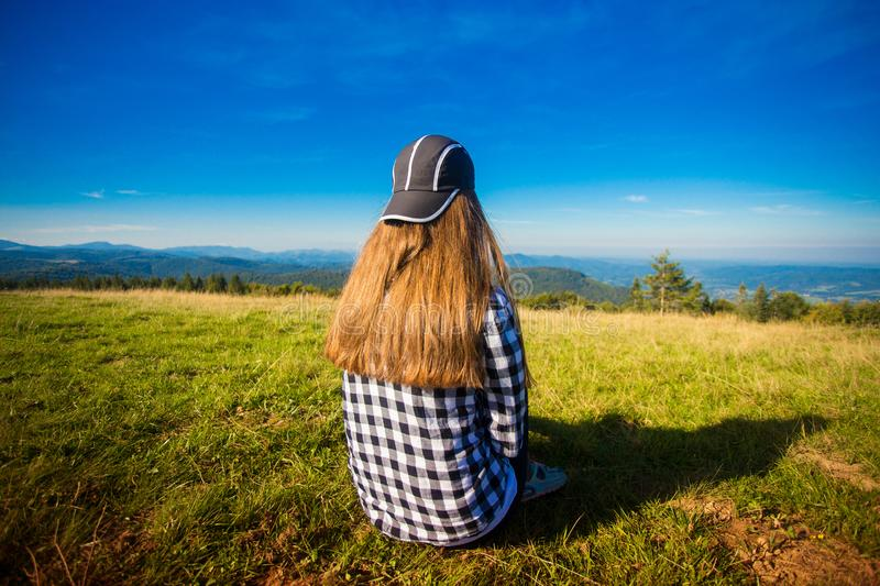 Woman tourist in cap on top of hill enjoying view of mountains. Travel concept stock photography