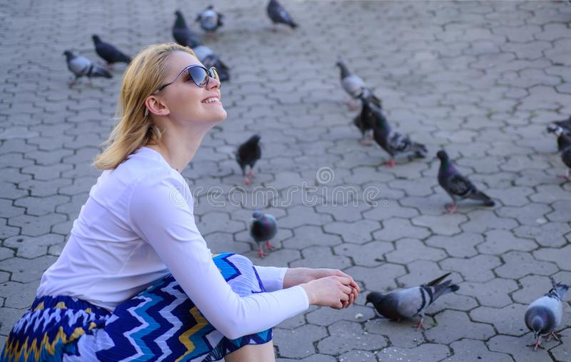 Woman tourist or citizen toss crumbs for pigeons. Girl feeding dove birds. Group doves on city square waiting treats royalty free stock images