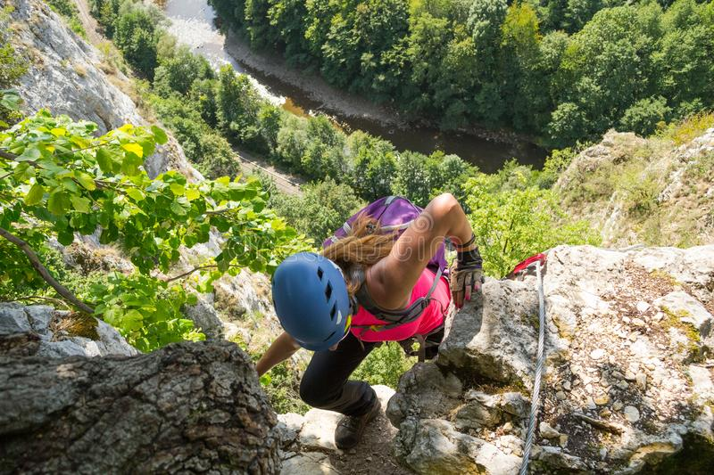 Woman tourist climbing a via ferrata route in Vadu Crisului, Apuseni mountains, Romania. Woman tourist climbing a via ferrata route called `Casa Zmeului`, in stock photo