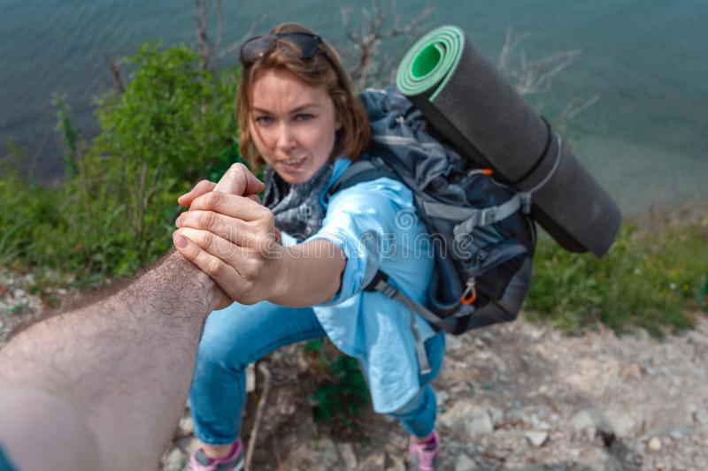 Woman tourist grabs the hand of his friend. In the background, the precipice and the sea. The concept of friendship and mutual royalty free stock photo