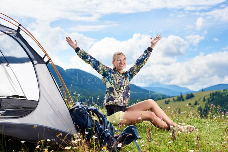 Woman tourist hiking in mountain trail, enjoying summer sunny morning in mountains near tent royalty free stock photography
