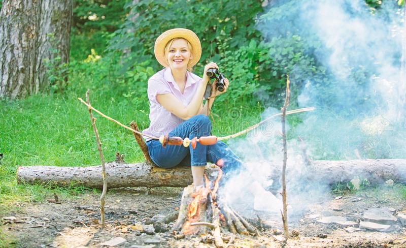 Woman tourist holds binoculars while sits on log near bonfire. Observing nature concept. Girl enjoy hike in forest. Observing nature. Her hobby is ornithology stock photography