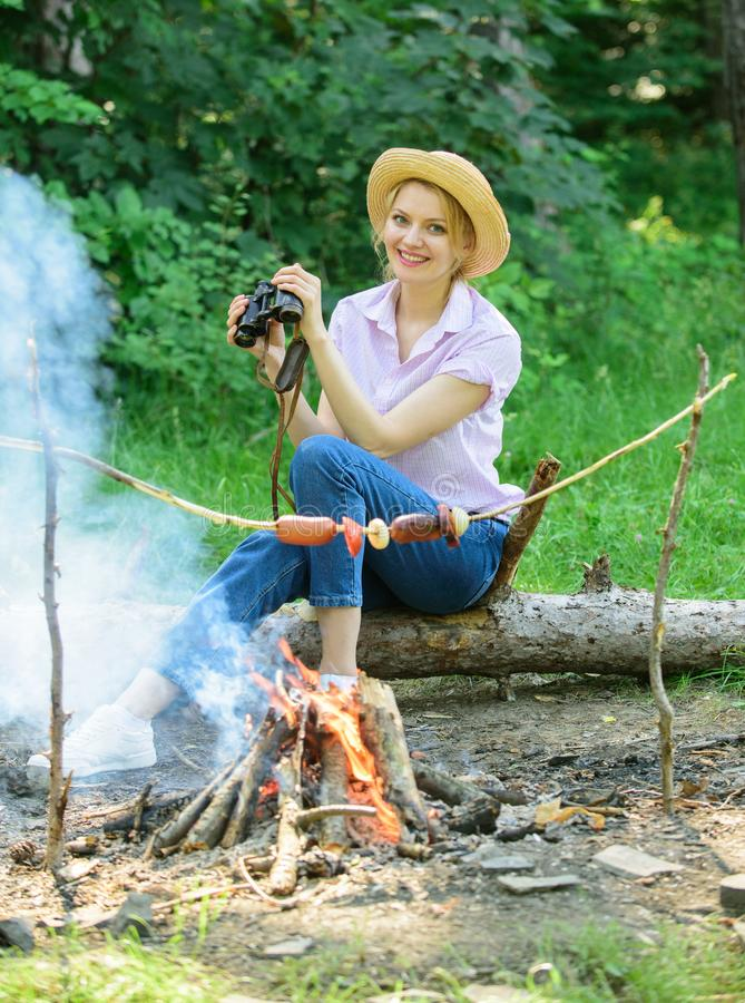 Woman tourist holds binoculars while sits on log near bonfire. Observing nature concept. Girl ornithology expedition in. Forest. Girl enjoy hike in forest stock photos