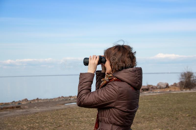Woman tourist looking through binoculars at distant sea, enjoying landscape. Autumnal time.Lonely woman in brown coat stock images