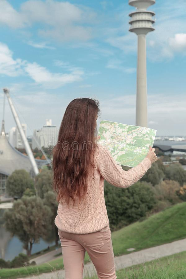 Woman tourist looking at the map in green park of european city, travel to Munich, Europe. Back view of Casual girl wearing in pi. Nk style outfit stock photo