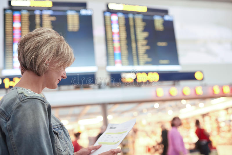 Woman tourist looking at timetable in airport stock photography