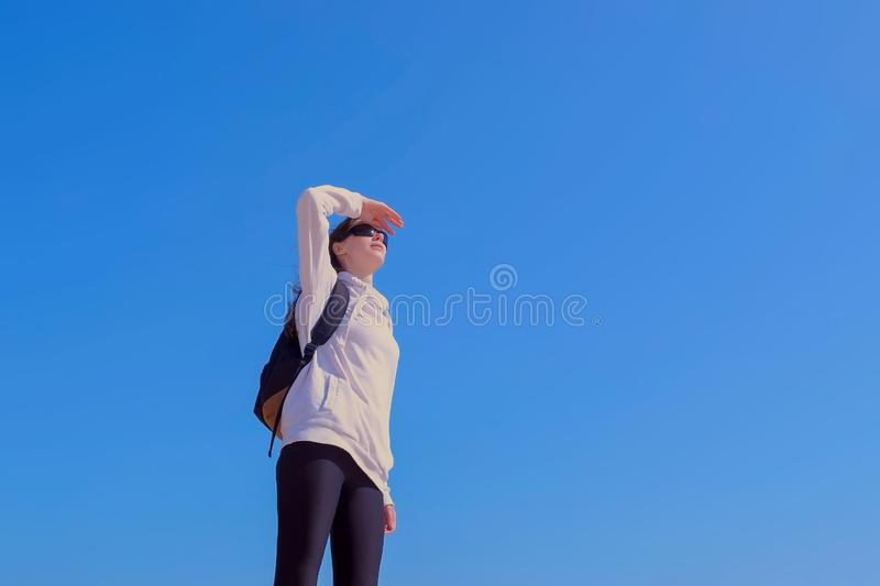 Woman tourist looks on sides on blue sky background hiking outdoors on vacation. Woman traveller in sunglasses is looking into the distance on the sides putting stock photography