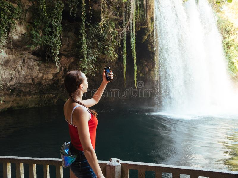 Woman tourist making photo with smartphone at upper Duden waterfall in Antalya, Turkey stock photos
