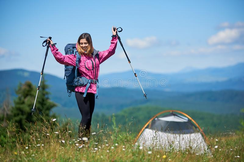 Woman tourist near camping in the mountains with backpack and trekking sticks in the morning. Happy woman tourist with backpack and trekking sticks near tent stock photos