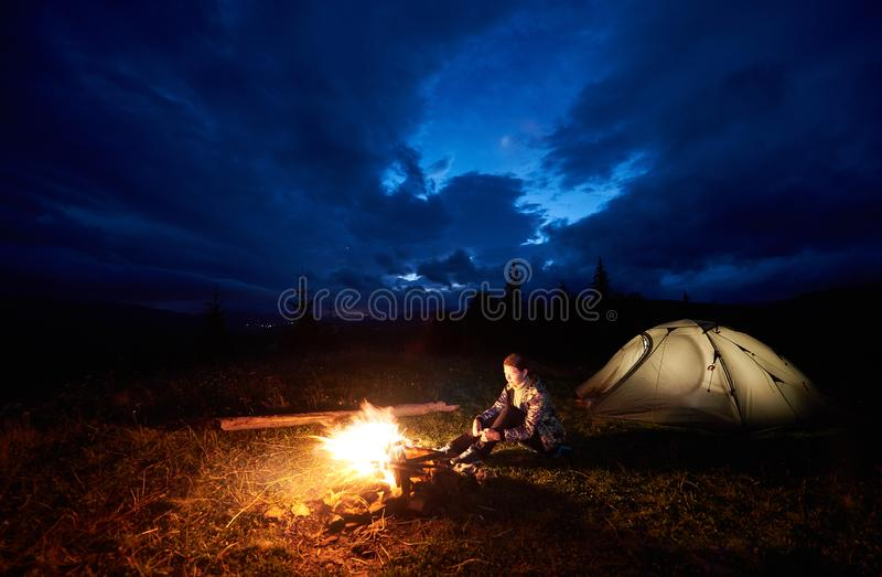 Woman tourist resting at night camping in mountains near campfire and tent under evening cloudy sky stock photos