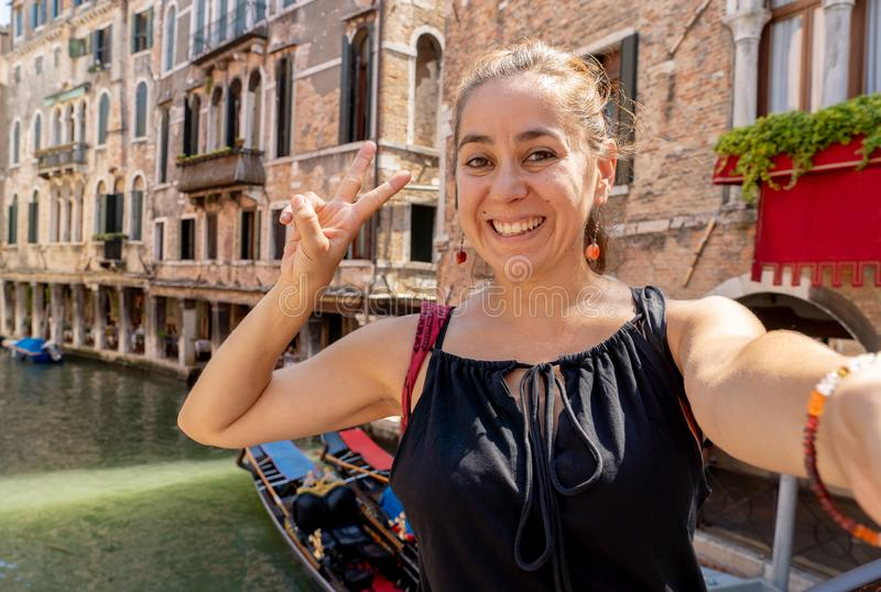 Woman tourist showing Victory and smiling while taking a selfie at the canal in Venice Italy. Young attractive latin hispanic tourist taking selfie at venice royalty free stock photo