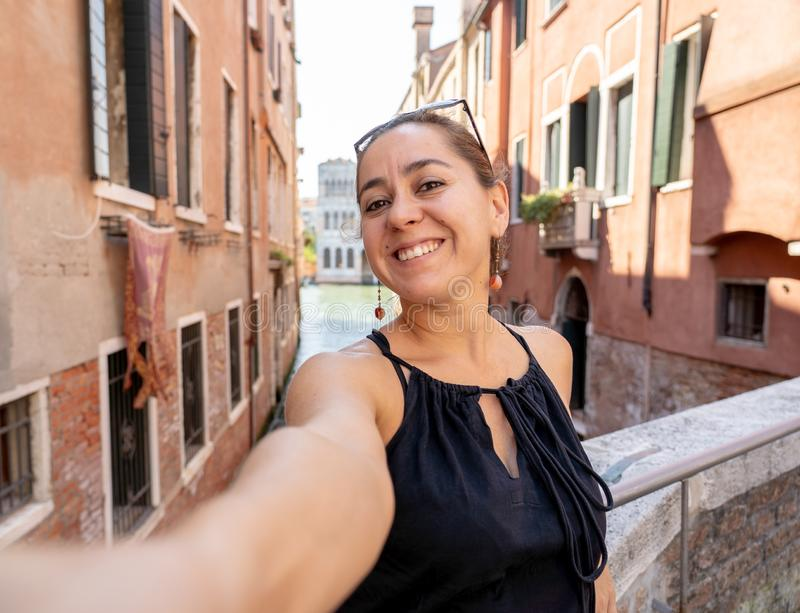 Woman tourist showing Victory while taking a selfie at the canal in Venice Italy. Young attractive latin hispanic tourist taking selfie at venice canal having stock photography