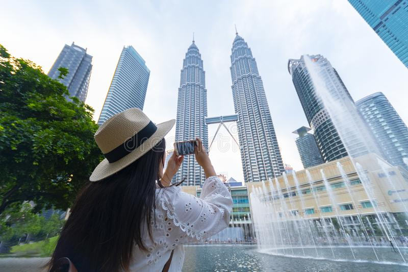 A woman tourist is sightseeing the Petronas Twin tower KLCC in Kuala Lumpur. stock photography