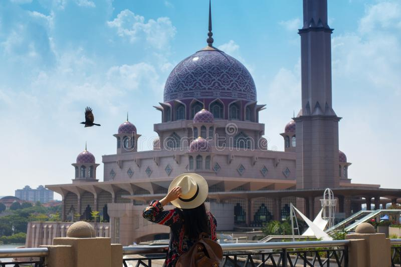 Woman tourist is sightseeing Putrajaya Mosque during travel stock photo