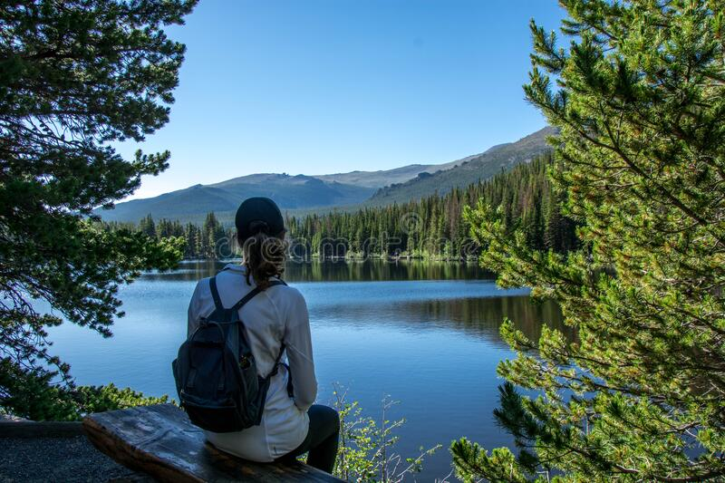 Woman sitting at bear lake in spring summer in the rocky mountain national park, colorado united states of america. Woman tourist sitting at beautiful bear lake royalty free stock photography
