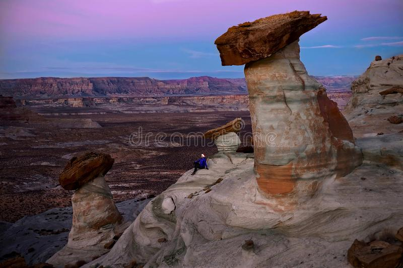 Woman tourist sitting on rock watching sunset. Giant toadstool rocks near Lake Powell in Arizona at sunset. Winter travel to Southwest of United States of stock photography