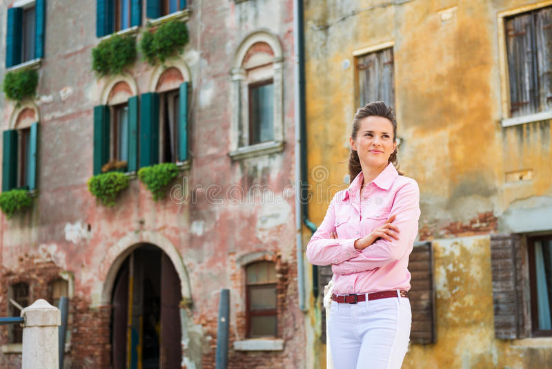 Woman tourist standing with arms crossed near Venice canal. Relaxing, an elegant female tourist is standing with her arms crossed near a Venice canal. Everything royalty free stock photography