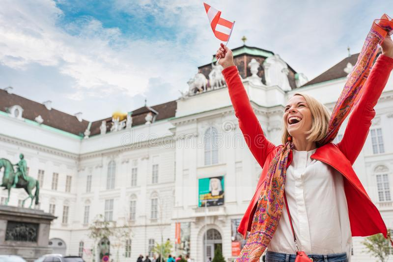 Woman tourist stands against the backdrop of the Austrian National Library in Vienna with raised arms and the flag of stock photography
