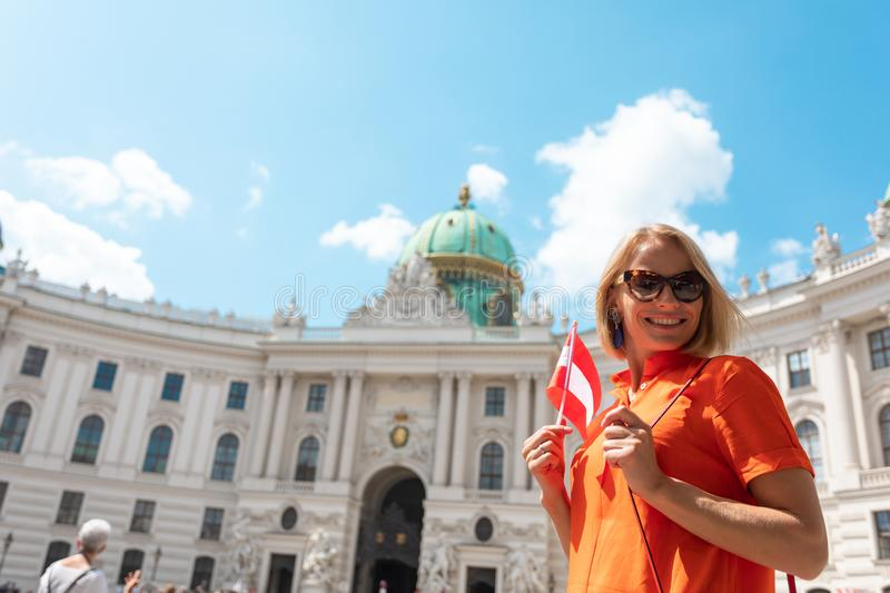 Woman tourist stands with flag of Austria at the Michaelplatz against the background of the building of the palace royalty free stock photos