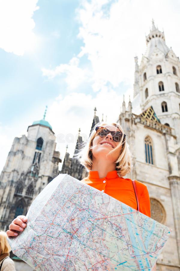 A young woman in a bright orange dress stands on the background of St. Stephen`s Cathedral in Vienna, Austria stock photos