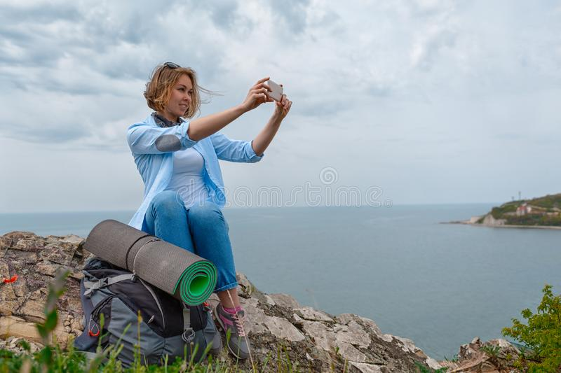 Woman tourist stopped and decided to take a photo of the landscape on the phone. Sea and sky with clouds on the background.  royalty free stock images
