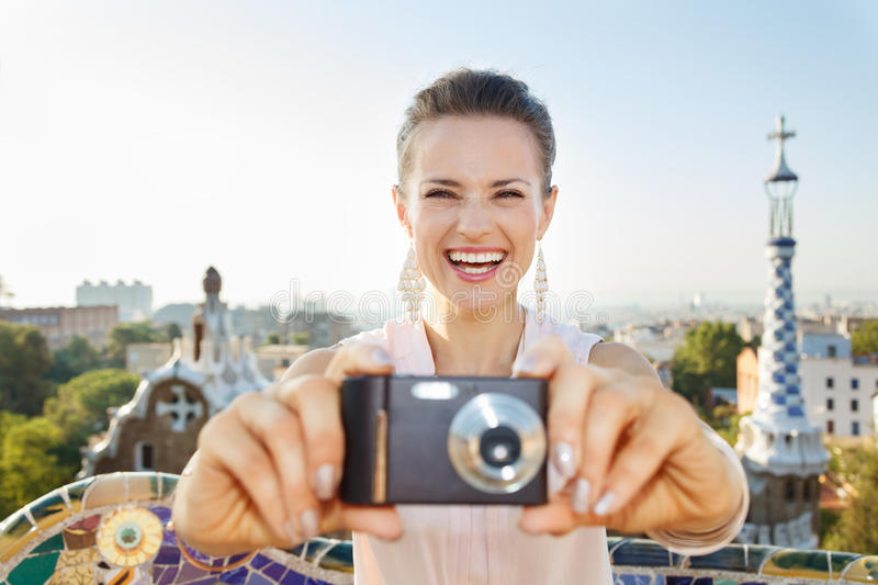 Woman tourist taking photo with photo camera in Park Guell. Refreshing promenade in unique Park Guell style in Barcelona, Spain. Smiling young woman tourist royalty free stock photos