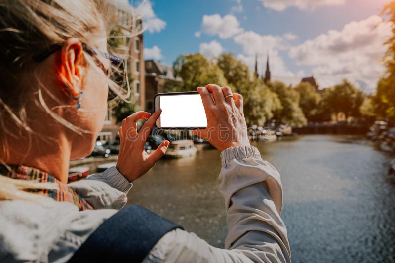 Woman tourist taking a picture of canal in Amsterdam on the mobile phone. Warm gold afternoon sunlight. Travel in Europe royalty free stock images