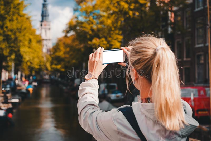 Woman tourist taking a picture of canal in Amsterdam on the mobile phone. Warm gold afternoon sunlight. Travel in Europe stock image