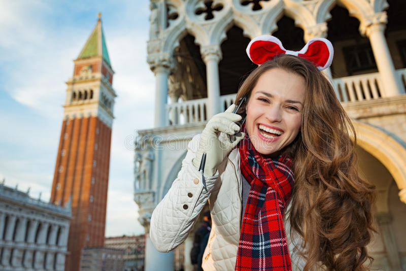 Woman tourist talking mobile while on Christmas in Venice, Italy. Christmas season brings spirit of travel. Smiling young woman tourist talking cell phone while royalty free stock photos