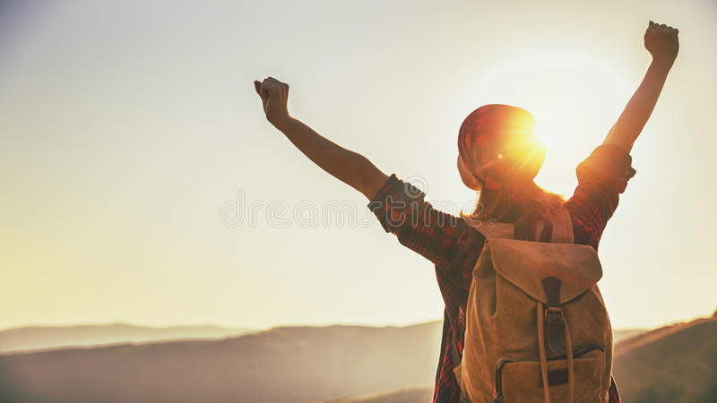 Woman tourist at top of mountain at sunset outdoors during hike stock photography