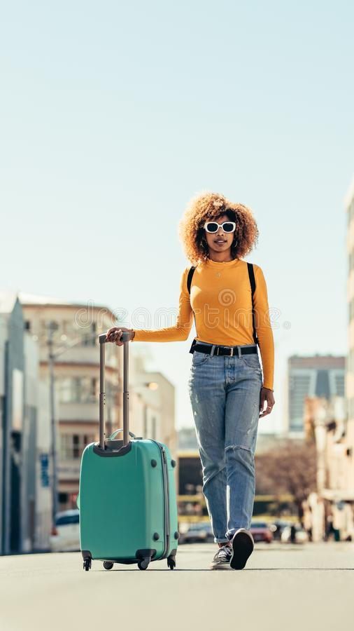 Woman tourist walking on street with luggage. Afro american woman traveller walking on street holding a luggage trolley. Woman in sunglasses carrying a backpack stock images
