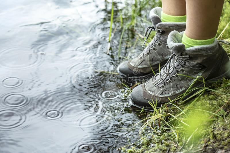 Woman in tourist waterproof hiking boots is standing on the shore of a lake, right next to the water in the rain. Close-up stock photo