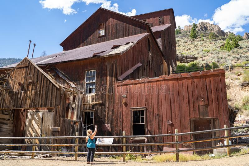 Woman tourists explores the old mining ghost town of Bayhorse Idaho in the Salmon-Challis National Forest.  stock photos