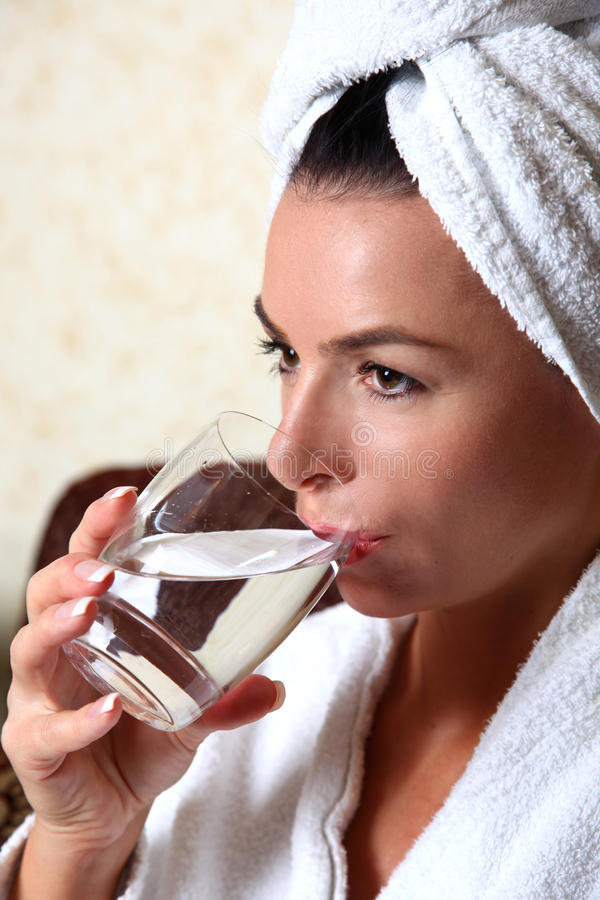 Woman in towel drinking water. Woman in white towel drinking water stock image