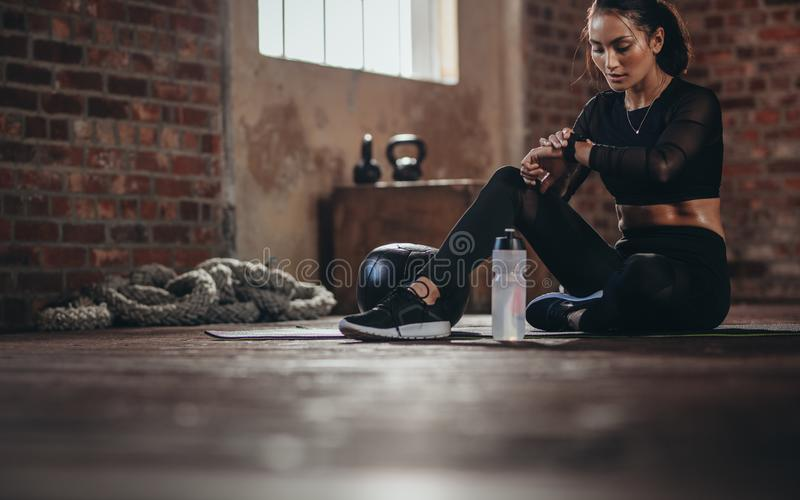 Woman tracking fitness progress on smart phone royalty free stock photos