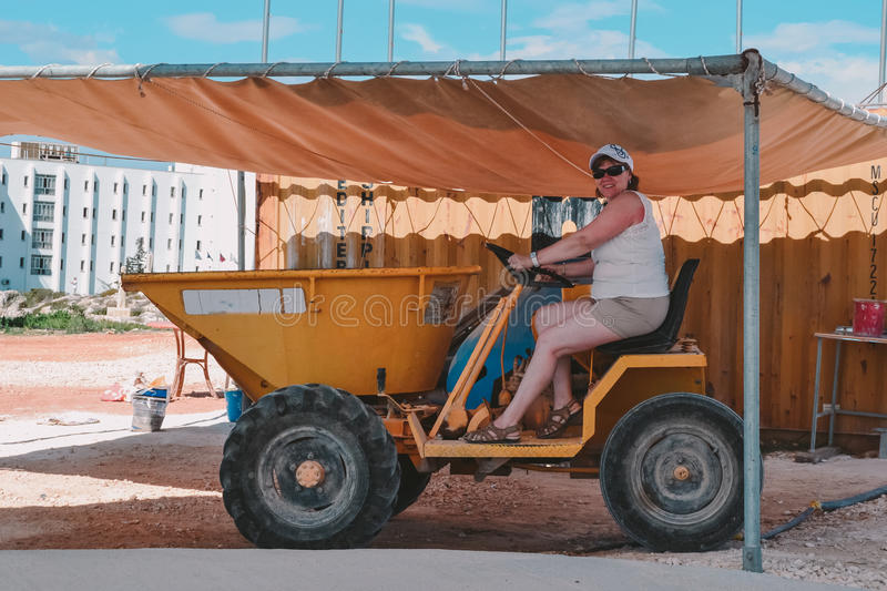 Woman in a tractor. Woman middle-aged tourist photographed the tractor on vacation stock image