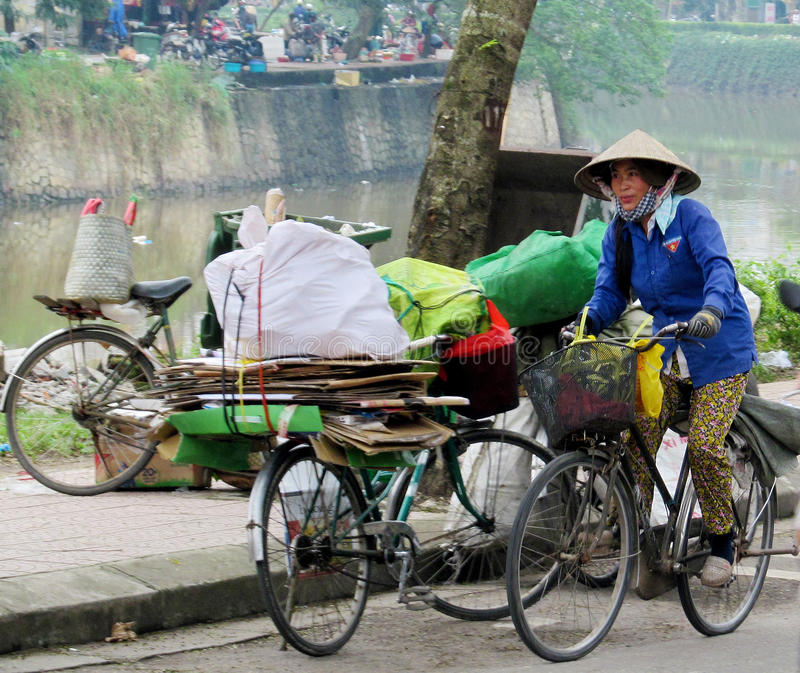 Woman in traditional Asian conical hat on bycicle royalty free stock photos