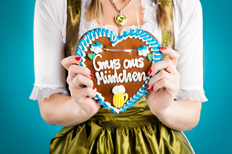 Woman in traditional Bavarian clothes from Munich. Young woman in traditional Bavarian clothes - dirndl or tracht with a gingerbread souvenir heart royalty free stock images