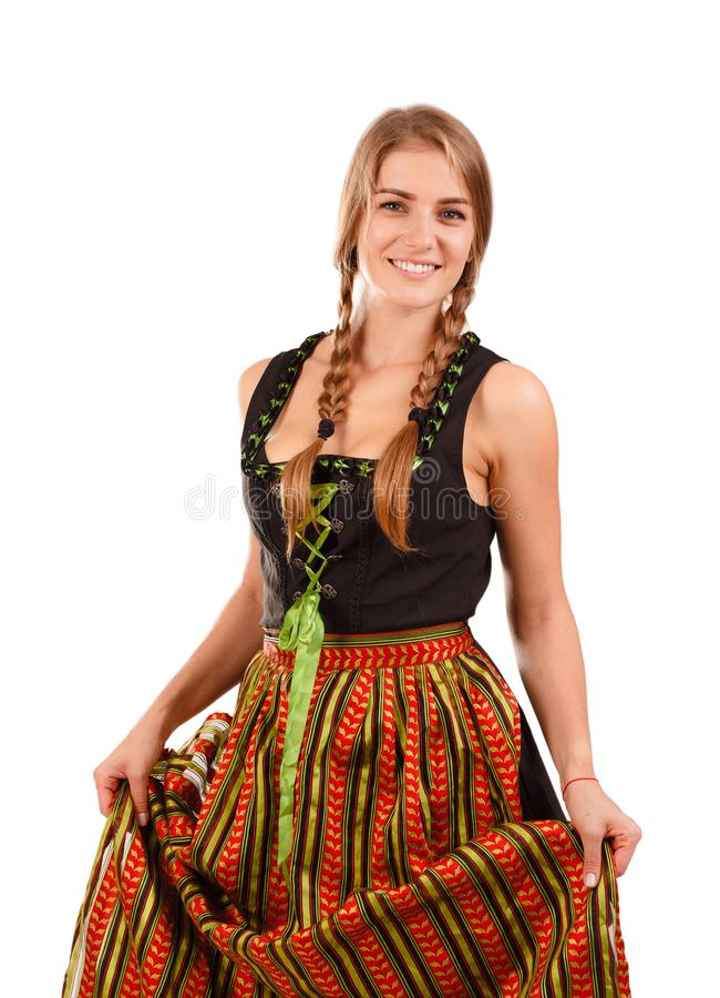 Woman in traditional bavarian dress. Isolated on white. German or Bavarian waitress with her hair in pigtails wearing a traditional dirndl. Oktoberfest concept royalty free stock photography