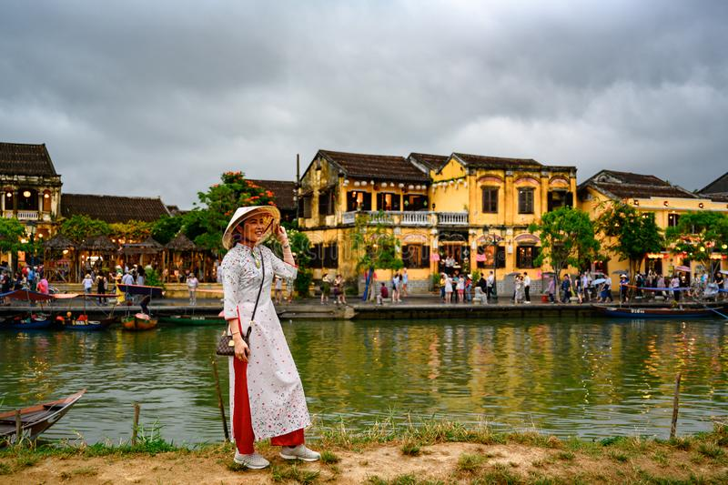 Asian woman posing for photos on canal in tourist destination Hoi An, Vietnamese women in Hoi An, Vietnam. Woman in traditional clothes taking photo with boats royalty free stock photo