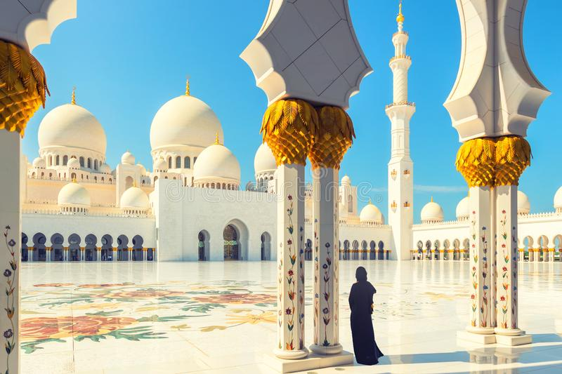 Woman in traditional dress inside Sheikh Zayed Mosque – tourist wearing black abaya visiting famous arabian religious temple stock photos